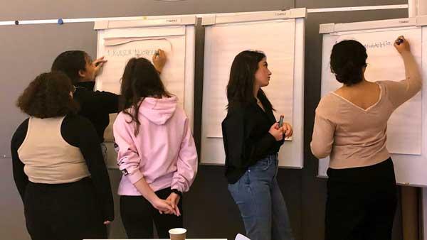 Viisi opiskelijaa kirjoittaa fläppitauluille ajatuksiaan työpajan kysymyksistä..